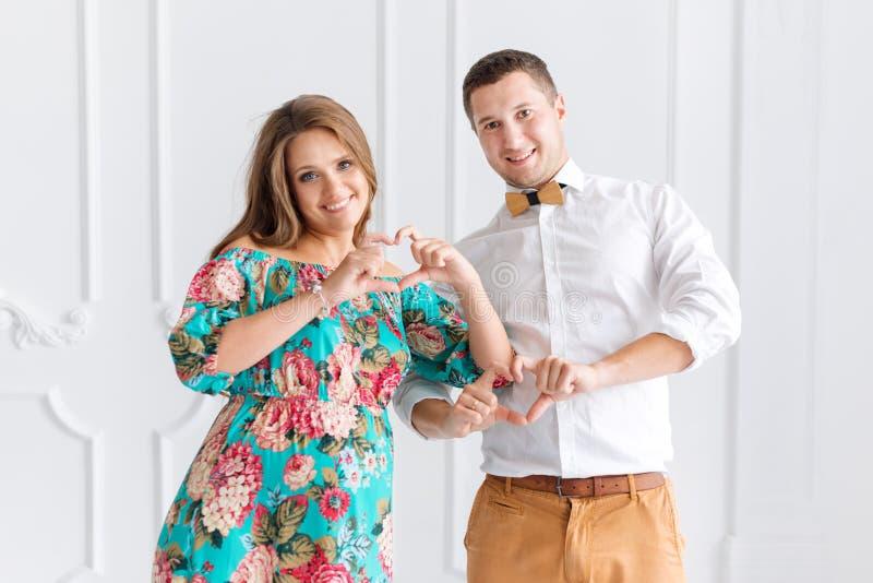Mooi zwanger gelukkig paar samen verwachtend een kind Man en vrouw in wit minimalistic binnenland die harten met handen tonen stock afbeelding