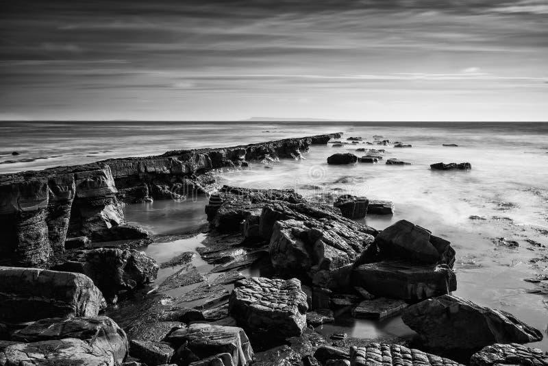 Mooi zwart-wit landschap van rotsachtige kust bij zonsondergang royalty-vrije stock fotografie
