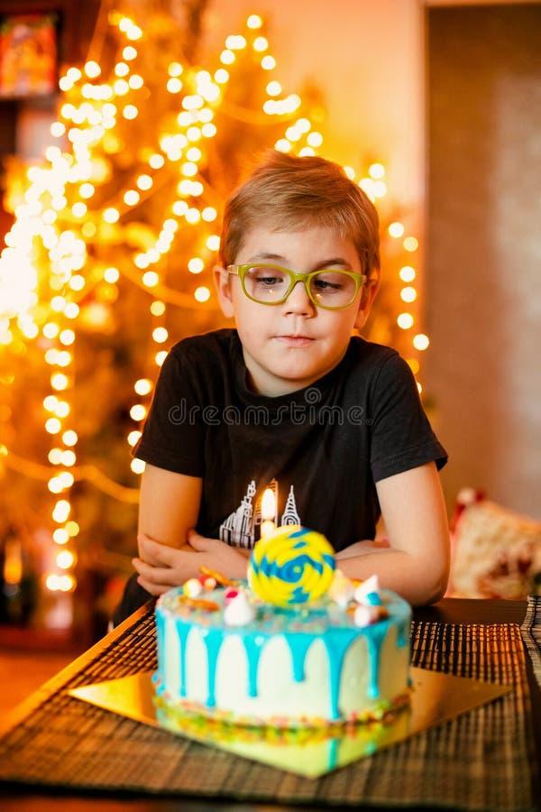Mooie aanbiddelijke zeven acht ??njarigenjongen die in grijs overhemd, zijn verjaardag vieren, blazend kaarsen op eigengemaakte g stock afbeeldingen
