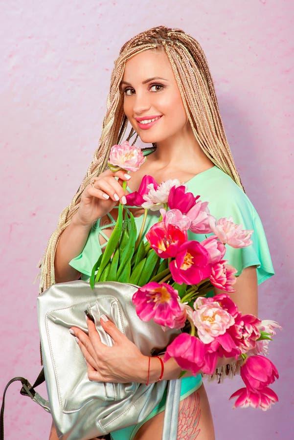Mooie aantrekkelijke blonde jonge vrouw met Afrikaanse vlechten met tulpen op roze achtergrond stock afbeeldingen