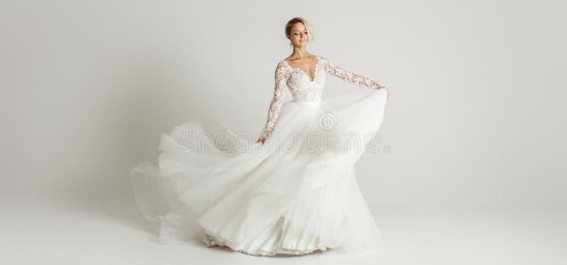 Mooie aantrekkelijke bruid in huwelijkskleding met lange volledige rok, witte achtergrond, dans en glimlach royalty-vrije stock afbeeldingen