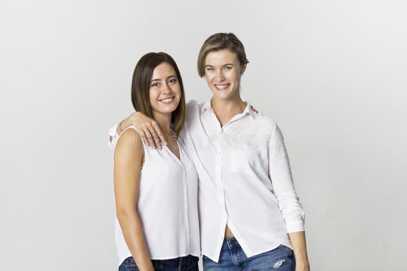 Mooie aantrekkelijke grappige ontspannen onbezorgde meisjes in wit die overhemd en jeans op witte achtergrond worden geïsoleerd royalty-vrije stock afbeelding