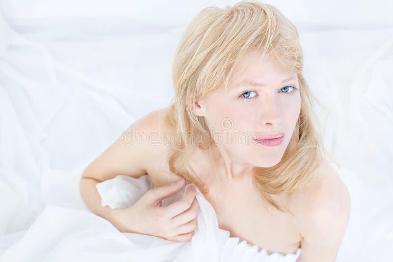 Mooie aantrekkelijke jonge vrouw (dicht omhooggaand gezicht) in witte kleding met Kaukasische gezonde huid, blond haar, blauwe og stock foto