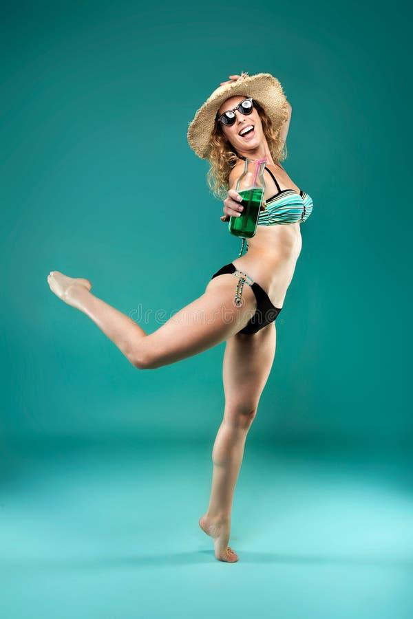 Mooie aantrekkelijke jonge vrouw met zonnebril in bikini die en groen sap springen houden stock foto's