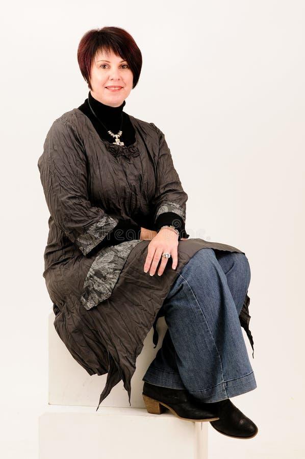 Mooie aantrekkelijke rijpe vrouwenzitting in jeans royalty-vrije stock fotografie
