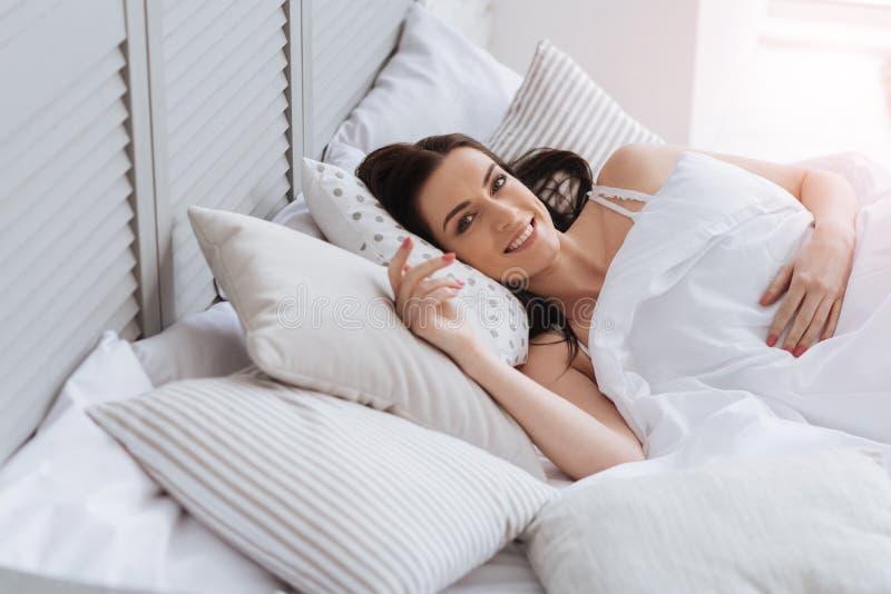 Mooie aantrekkelijke vrouw die in het bed liggen stock foto's