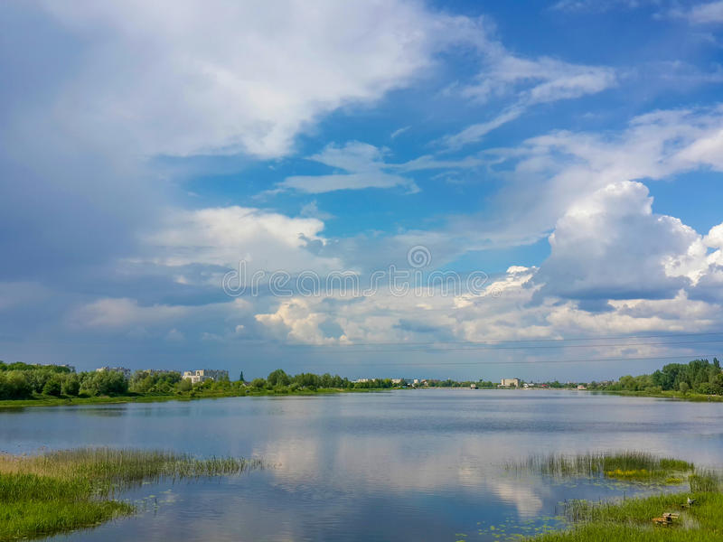 Mooie aard, rivier en bewolkte blauwe hemel stock foto's