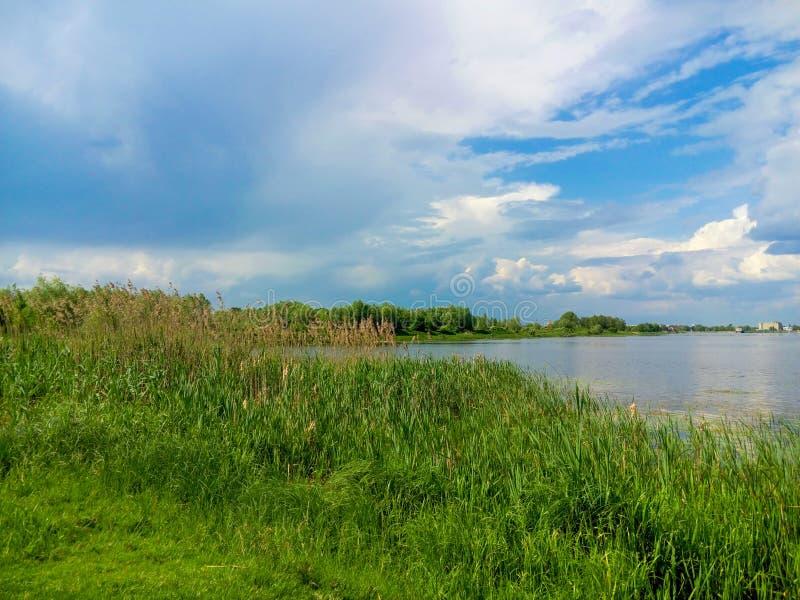 Mooie aard, rivier en bewolkte blauwe hemel stock foto
