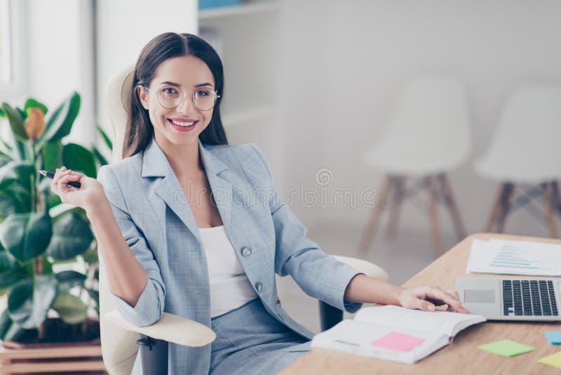 Mooie, aardige, leuke, perfecte vrouwenzitting bij haar bureau op leer royalty-vrije stock afbeelding