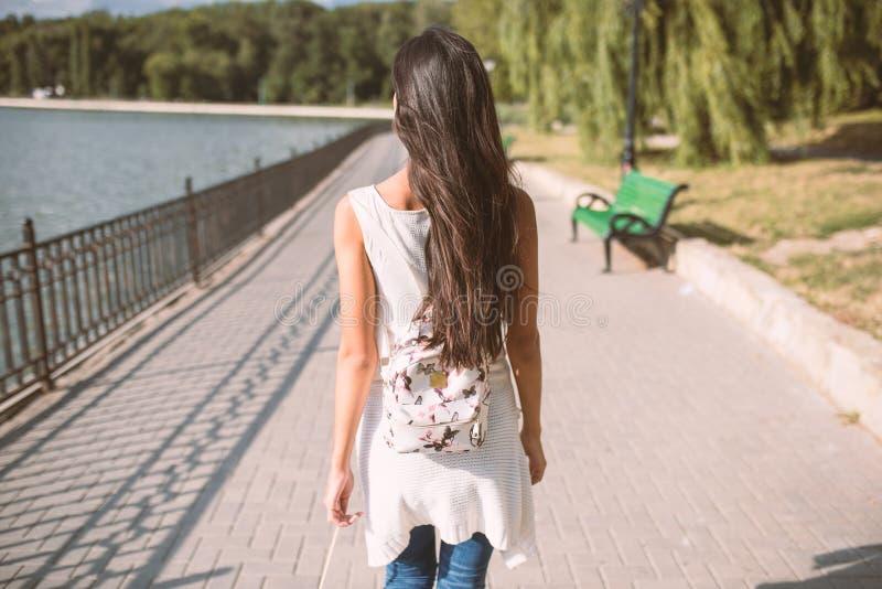 Mooie achtermening die van jonge brunttevrouw met lang haar en met rugzak, in het park met meer lopen Reis stock afbeelding