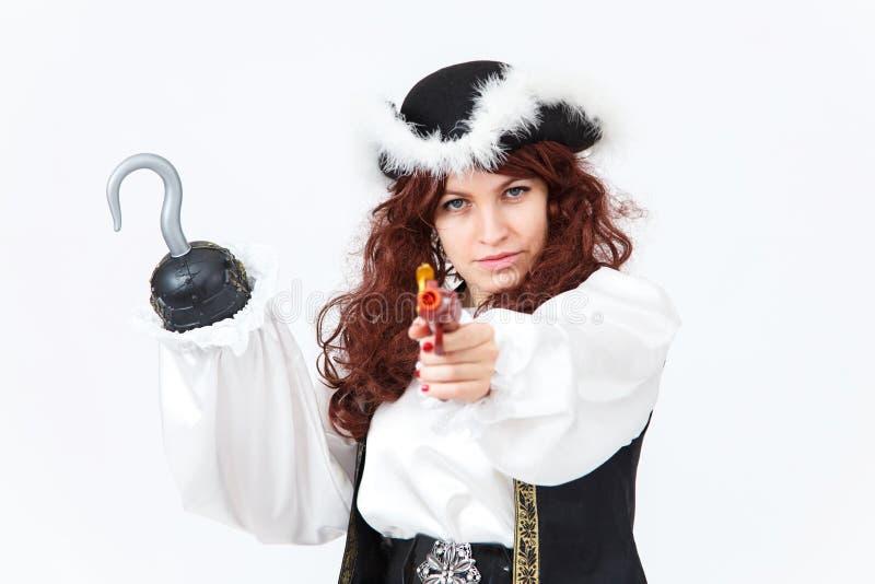 Mooie actrice in piraatkostuum met pistool en haak stock afbeelding
