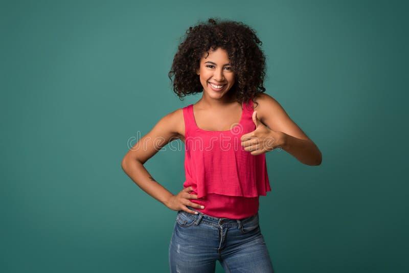 Mooie Afrikaans-Amerikaanse vrouw die duim op achtergrond tonen stock fotografie