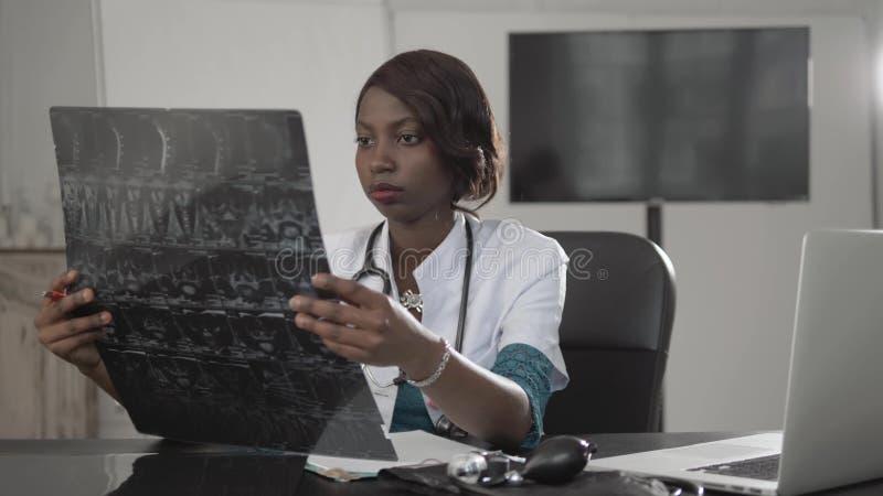 Mooie Afrikaanse Amerikaanse gezondheidszorgarbeider met x-ray, medisch internationaal concept, het zwarte arts modern denken, stock afbeelding