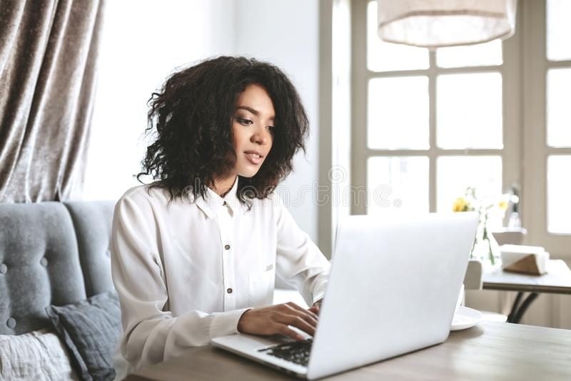 Mooie Afrikaanse Amerikaanse meisjeszitting in restaurant met laptop Mooi meisje die aan haar computer in koffie werken royalty-vrije stock afbeelding
