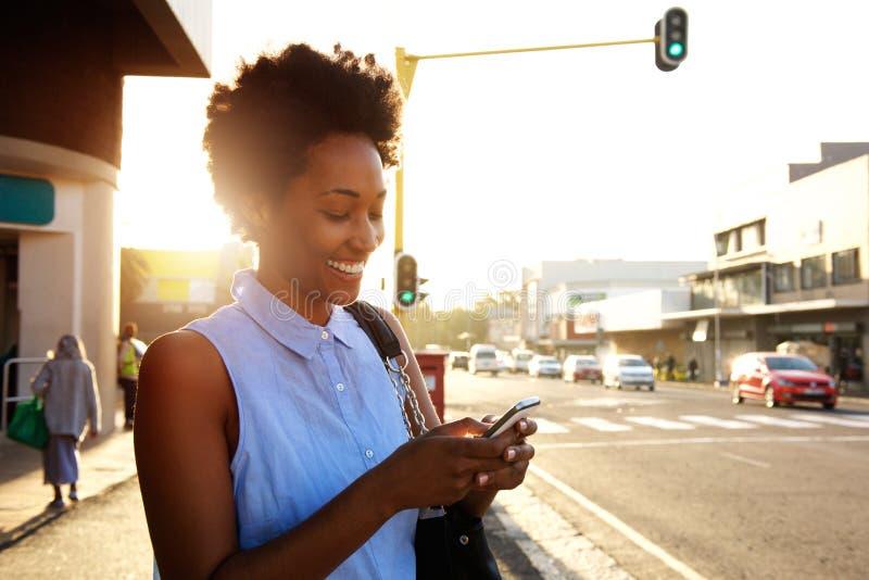 Mooie Afrikaanse vrouw die cellphone in openlucht gebruiken stock afbeelding