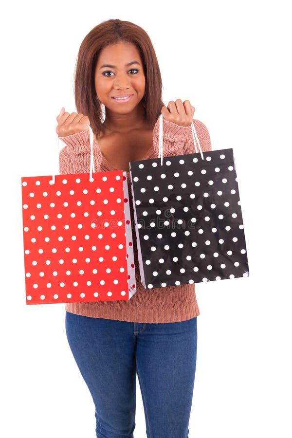 Mooie Afrikaanse vrouw die een creditcard en het winkelen zakken houden stock foto's