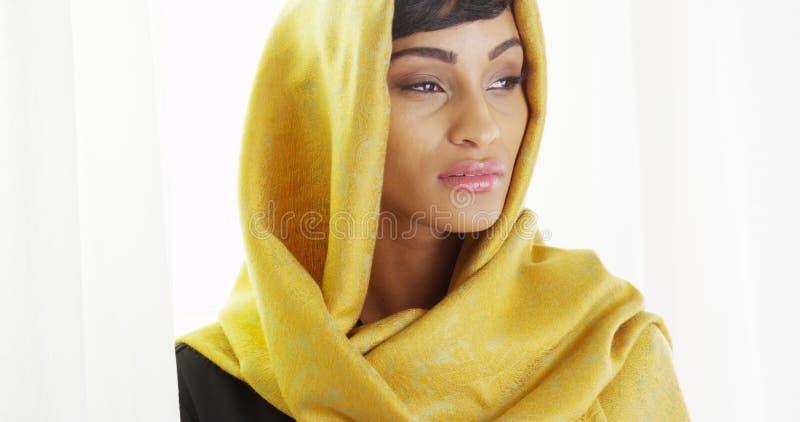 Mooie Afrikaanse vrouw die gouden hoofdsjaal in heldere ruimte dragen stock foto
