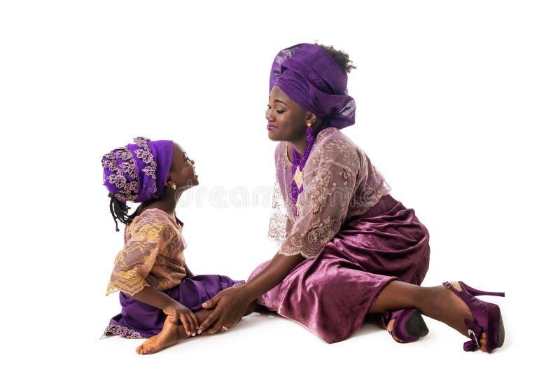 Mooie Afrikaanse vrouw en mooi meisje in traditionele kleding stock afbeelding