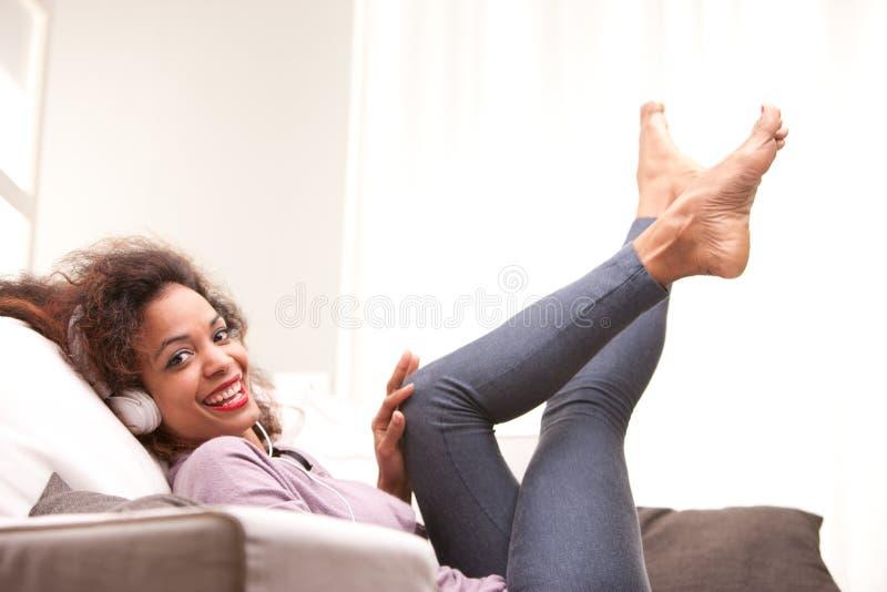 Mooie Afro-Amerikaanse vrouw op een bank royalty-vrije stock fotografie