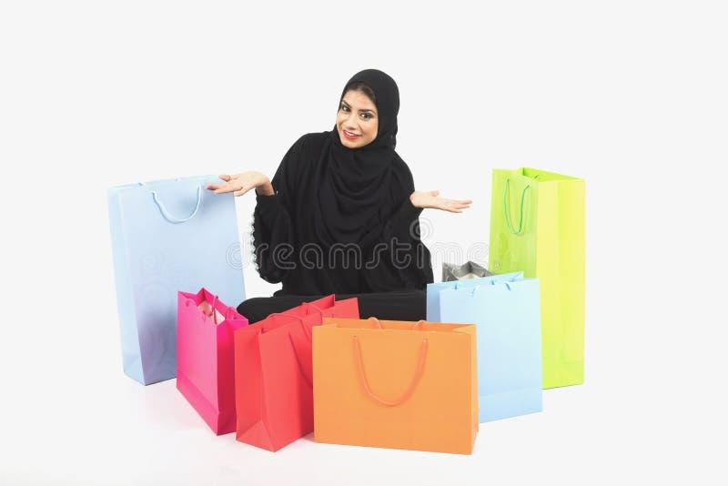 Mooie Arabische vrouwelijke zitting op de vloer na het winkelen stock afbeeldingen