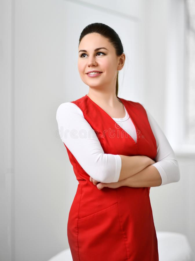 Mooie artsenschoonheidsspecialist in medische eenvormige rode medische die toga met handen in wit schoonheidsbureau worden gekrui royalty-vrije stock foto