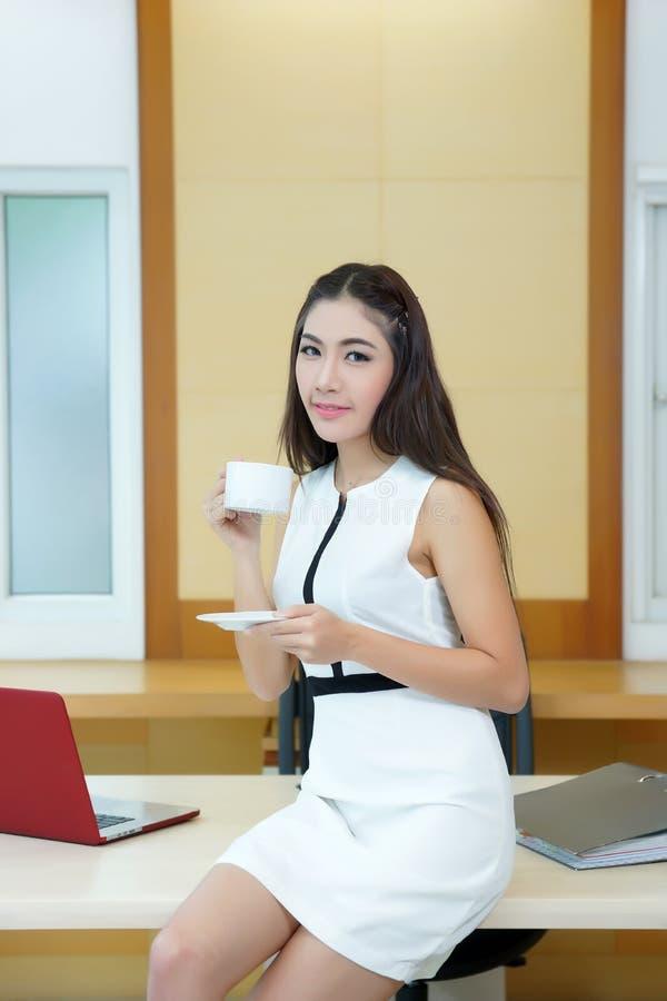 Mooie Aziatische de koffiekop van de bedrijfsvrouwenholding bij haar bureau stock foto