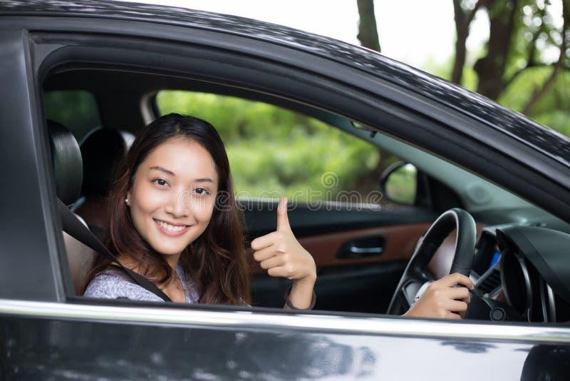 Mooie Aziatische en vrouw die glimlachen genieten van het drijven van een auto op weg stock foto's