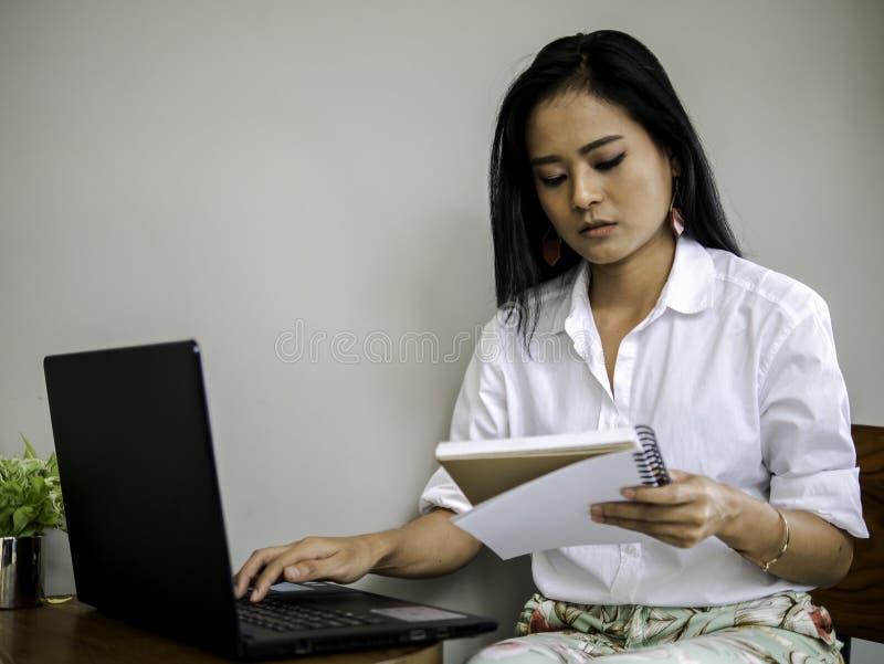 Mooie Aziatische freelancer die notaboek, dat op labtoptoetsenbord typt concentreert haar werk kijkt royalty-vrije stock foto
