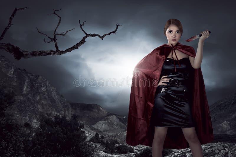 Mooie Aziatische heksenvrouw die bloedig mes houden royalty-vrije stock foto's