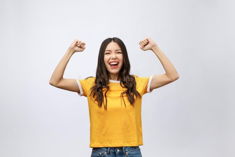 Mooie Aziatische jonge die vrouw en blij die van succes wordt opgewekt, over grijze achtergrond, carrière freelance zaken wordt g stock foto