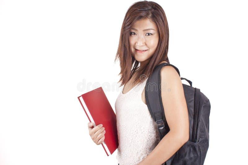 Mooie Aziatische jonge vrouw die met rugzak rood boek houden stock foto