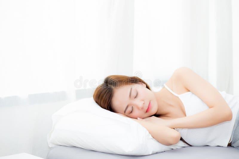Mooie Aziatische jonge vrouwenslaap die in bed met hoofd op comfortabel en gelukkig hoofdkussen liggen royalty-vrije stock foto