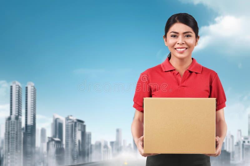 Mooie Aziatische leveringsvrouw die pakket leveren stock foto's