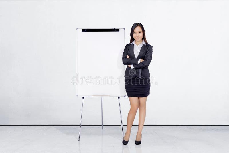 Mooie Aziatische onderneemster die zich met whiteboard bevinden royalty-vrije stock foto's