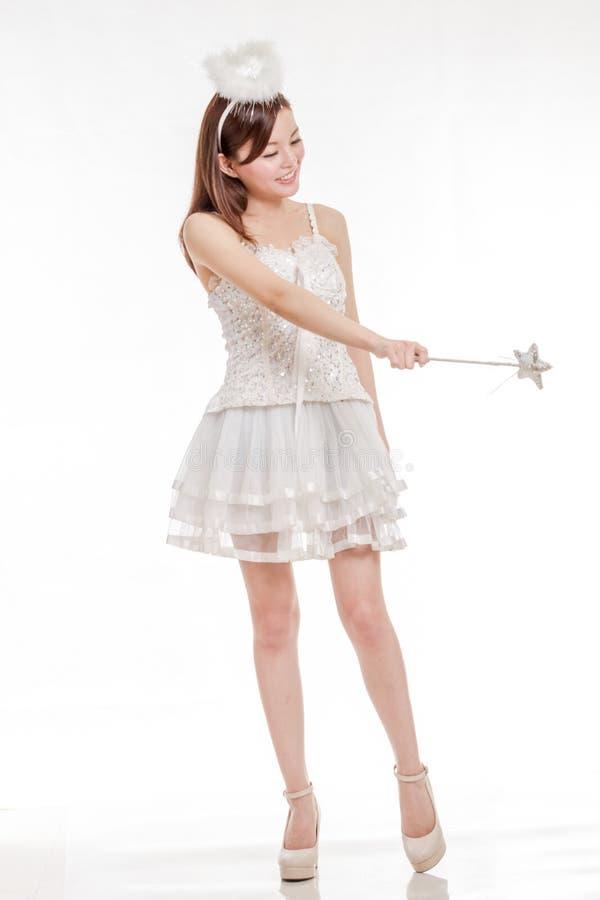 Mooie Aziatische Vrouw in Angel Costume, die haar toverstokje poiting stock foto