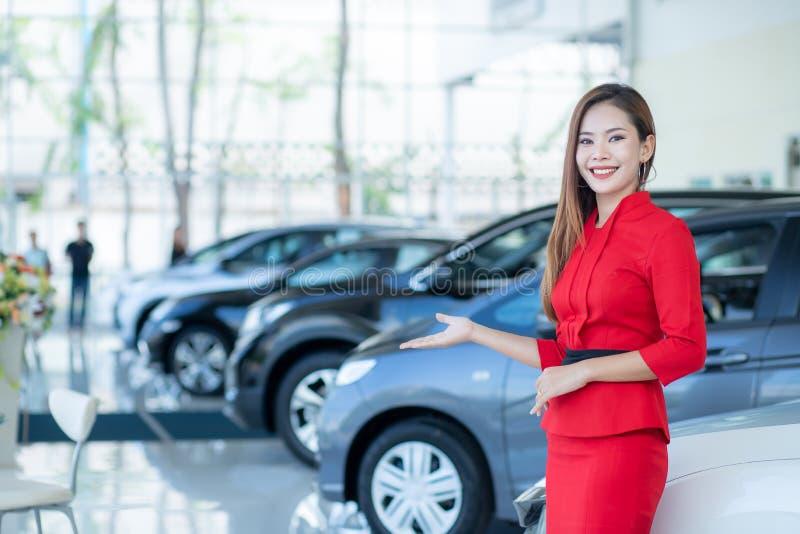 Mooie Aziatische vrouw of autoverkoper Stand die een nieuwe auto verre sleutel in de toonzaal, Auto's voor Verkoop houden stock fotografie