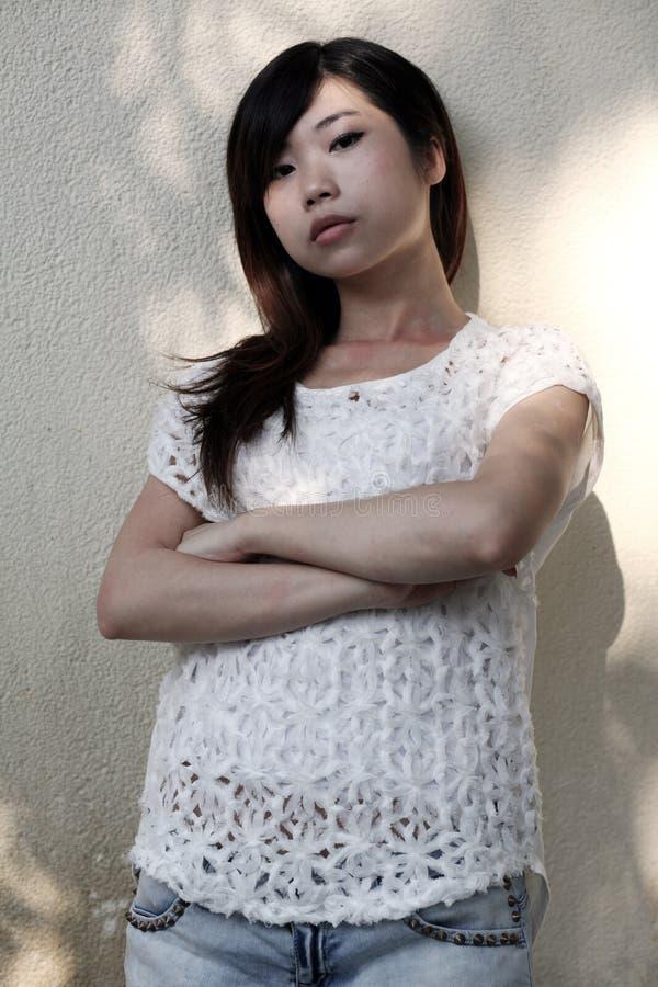Mooie Aziatische vrouw die de kijker met gevouwen wapens bekijken stock afbeelding