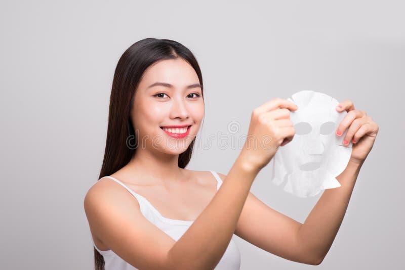 Mooie Aziatische vrouw die document bladmasker op haar gezichtswhit toepassen royalty-vrije stock afbeelding