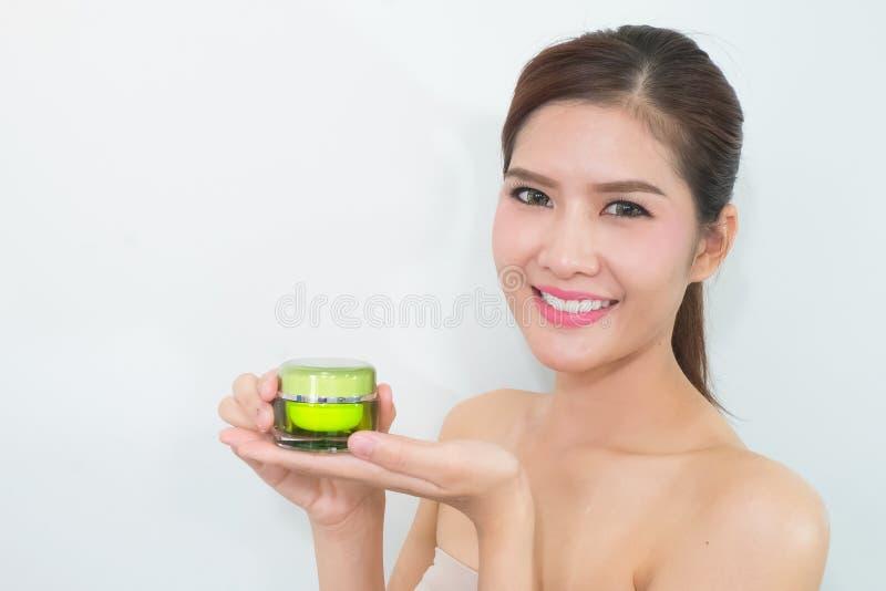 Mooie Aziatische vrouw die een de zorgproduct van de aardhuid, moisturi gebruiken royalty-vrije stock fotografie