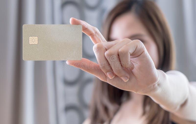 Mooie Aziatische vrouw die gouden creditcard houden stock fotografie