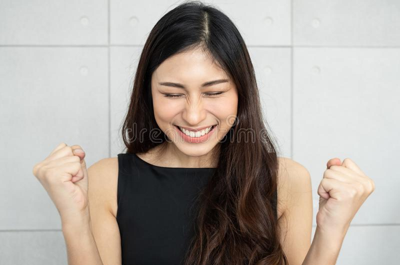 Mooie Aziatische vrouw die haar handen omhoog opheffen stock foto