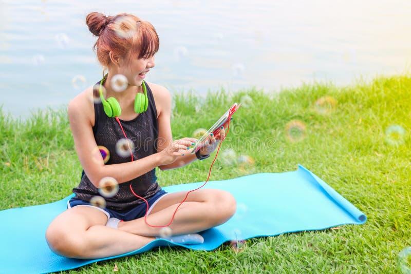 Mooie Aziatische vrouw die hoofdtelefoons het luisteren muziek met smartphone of tablet op gras in openluchtpark gebruiken Aard i royalty-vrije stock afbeelding