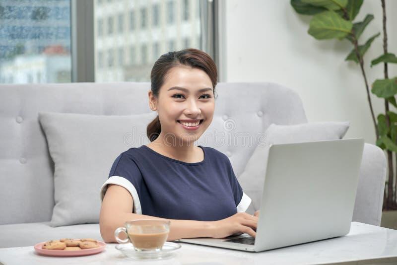 Mooie Aziatische vrouw die laptop computer met behulp van stock afbeelding