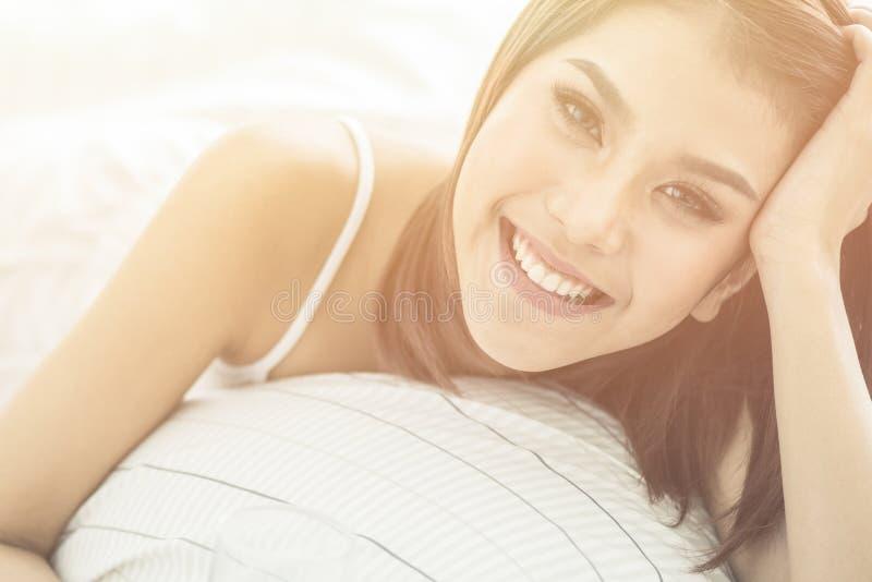 Mooie Aziatische vrouw die op het bed liggen Zij is zeer gelukkig stock foto