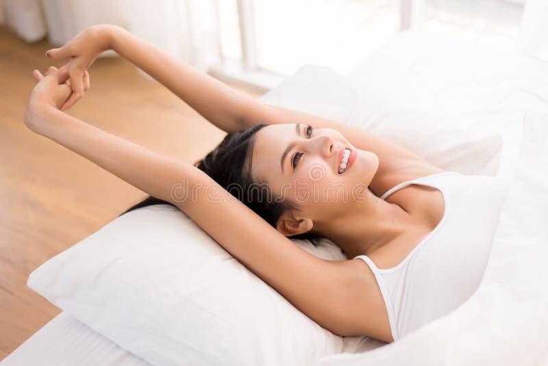 Mooie aziatische vrouw die 's morgens in haar slaapkamer staat en wakker wordt, gelukkig en glimlachend stock foto's