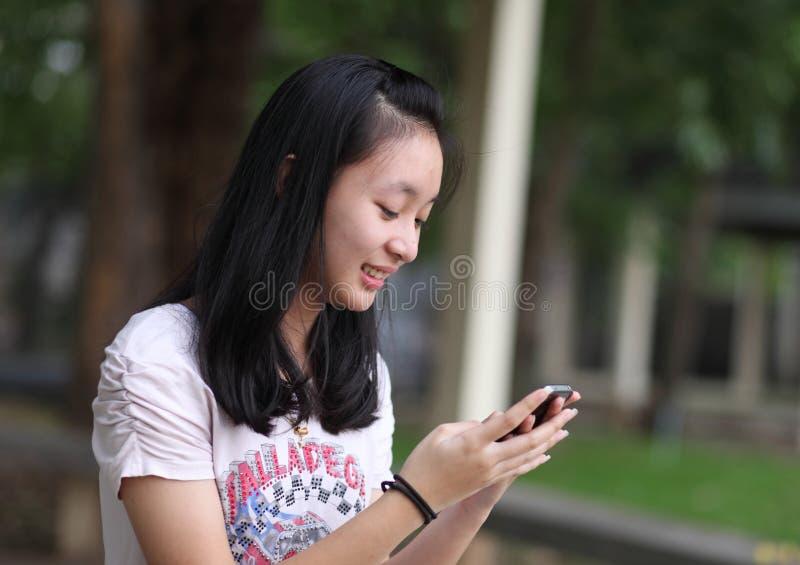 Mooie Aziatische vrouw die slimme telefoon in het park met behulp van royalty-vrije stock foto