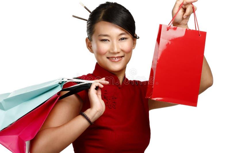Mooie Aziatische vrouw die veelkleurige het winkelen zakken tonen stock foto