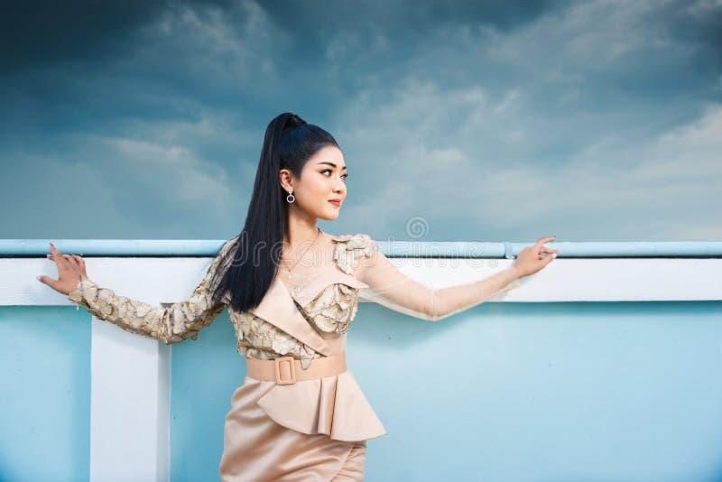 Mooie Aziatische vrouw die zich naast zwembad bevinden openlucht royalty-vrije stock foto