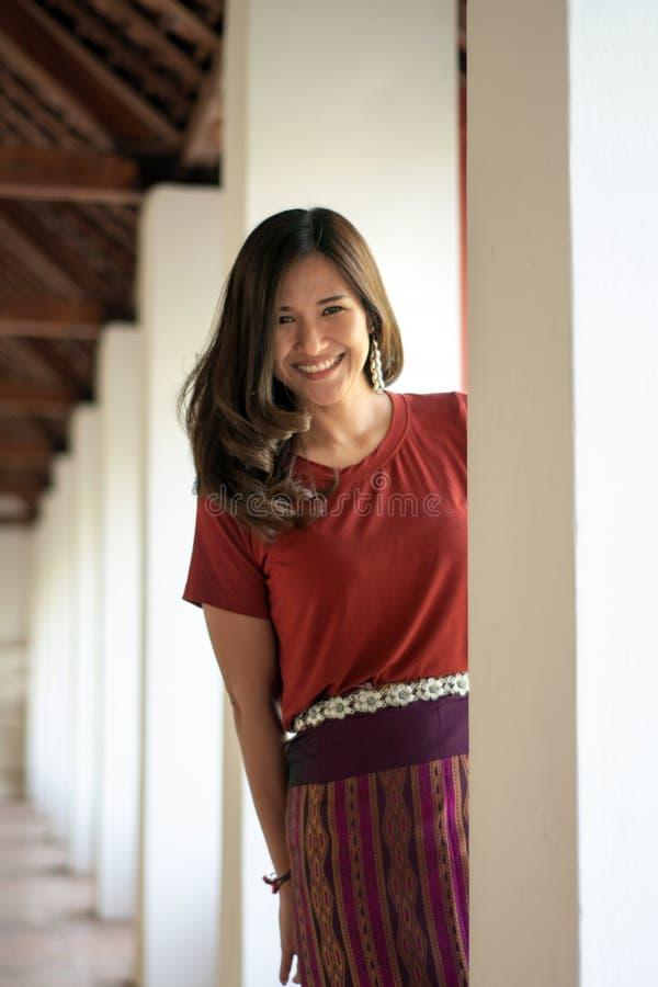 Mooie Aziatische vrouw door sarongen te dragen die camera op de vage achtergrond bekijken royalty-vrije stock fotografie