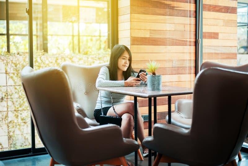 Mooie Aziatische vrouw gebruikend Internet met haar smartphone in restaurant, Gelukkig en glimlachend, het Positieve denken, Exem royalty-vrije stock afbeelding